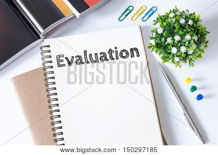 evaluation word message on white paper book and copy space on white desk / business concept / top view