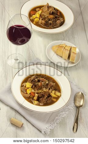 A photo of ox tail, rabo de toro, a traditional Spanish stew, served with bread and red wine