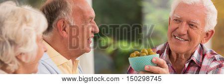Elder couple looking at their smiled senior friend