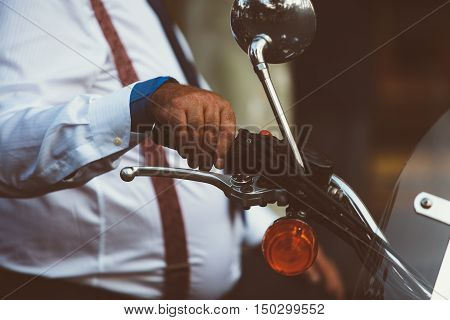 Close-up of unrecognizable adult man holding hand on motorcycle handle