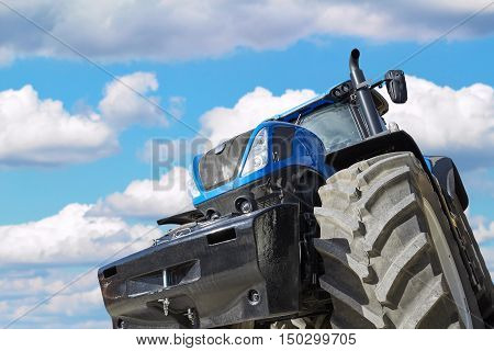 Tractor working on the farm, a modern agricultural transport, a farmer working in the field, tractor in the background cloudy sky, modern tractor closeup