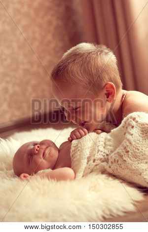 White European boy 5 years communicates with her newborn brother in a cozy room. Family values good attitude to children