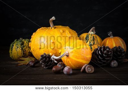 Festive autumn background. Pumpkins, pine cones and leaves at dark wooden table.