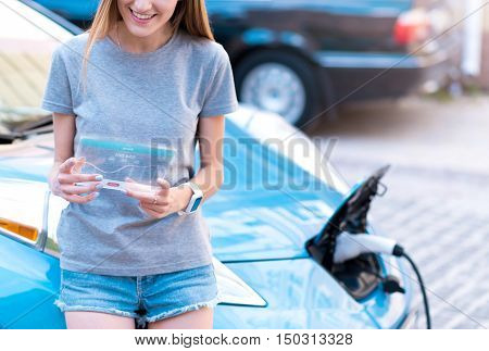 In pace with time. Cheeful young smiling woman standing near her car and using modern tablet