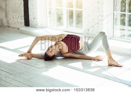 Beauty and calmness. Young athletic slim girl doing a yoga posture while developing her flexibility and having training.