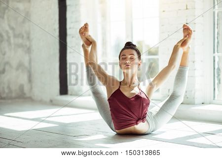 Calm and power. Young active delighted girl having her yoga exercises while doing a posture and improving her spine flexibility in a gym. poster