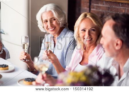 My lovely family. Elderly elegant delighted woman holding the wineglass and smiling while sitting on a kitchen with her family.