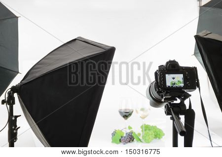 Professional SLR camera on a tripod takes a shot in the studio.