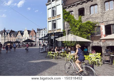 Ghent, Belgium, 27 august 2016: woman on bike passes outdoor café near groentenmarkt in centre of belgian city Ghent