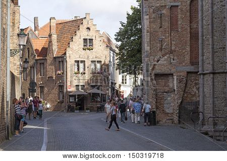 Bruges, Belgium, 28 august 2016: tourism in centre of old belgian city of bruges in flanders near old onze-lieve-vrouw church
