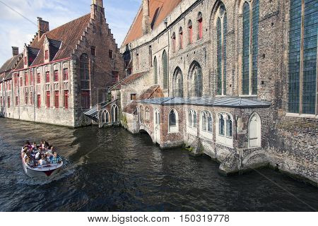 Bruges, Belgium, 28 august 2016: boat with tourists in Bruges canal near sint-Janshospitaal on sunny summer day