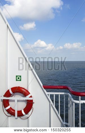 lifebuoy and part of white metal ship at sea with blue sky and clouds