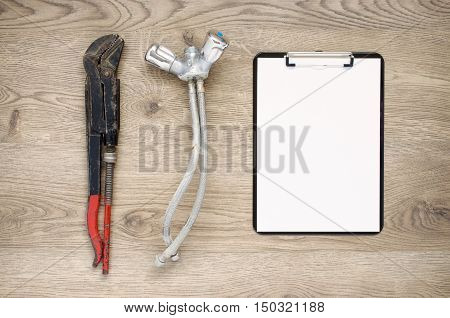 Rusty old plumbing tool and tap with clipboard