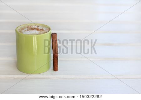frothy cappuccino with cinnamon in a green mug on a light wooden background / aromatic coffee break