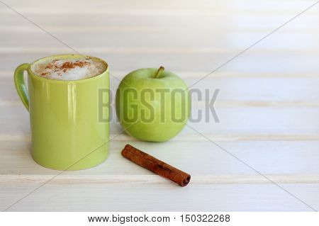 frothy cappuccino with cinnamon in a green mug and apple / coffee break for refreshment