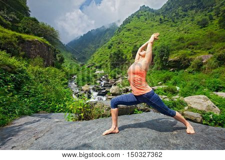 Yoga outdoors - sporty fit woman doing Ashtanga Vinyasa Yoga asana Virabhadrasana 1 Warrior pose posture at waterfall in HImalayas mountains
