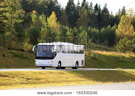 Landscape of forest with fall foliage and white coach bus traveling along road. Copy space for your text.