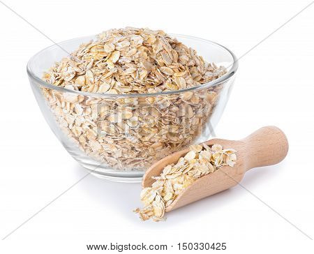 Oat flakes in glass bowl and wooden scoop isolated on white background. Healthy food. Healthy groats. Oatmeal. Oats in glass bowl isolated on white with clipping path