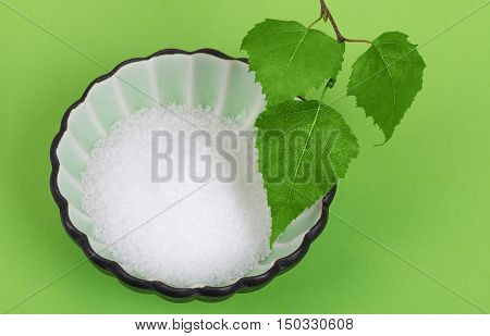 Xylitol birch sugar in white porcelain bowl with birch leaves over green. White granulated sugar alcohol, substitute used as sweetener that taste like table sugar, extracted from wood of birch trees.