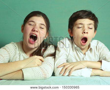 teen siblings brother and sister yawning close up portrait