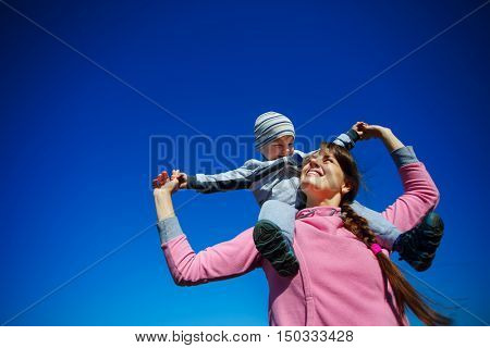 Mother with the son against the bright blue sky