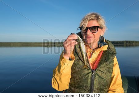 Blonde girl catched a smelt in the sea