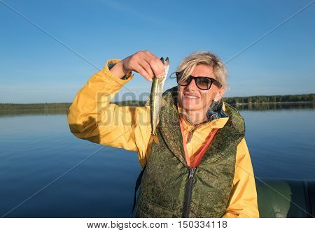Happy blonde girl catched a smelt in the sea