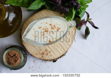 Classic European white sauce Bechamel in saucer with nutmeg, basil and olive oil on white background. Bechamel sauce for traditional European dishes. Italian food concept. Top view. Copy space.
