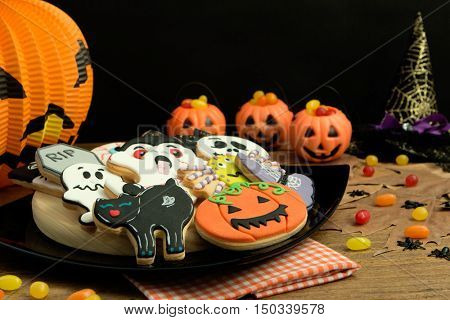 Creepy Halloween cookies and pumpkin baskets filled with candies on a wooden table