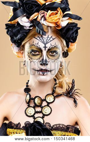 attractive young woman with sugar skull makeup,Dia de los Muertos - Mexican Day of the dead woman wearing sugar skull makeup and flower wreath.