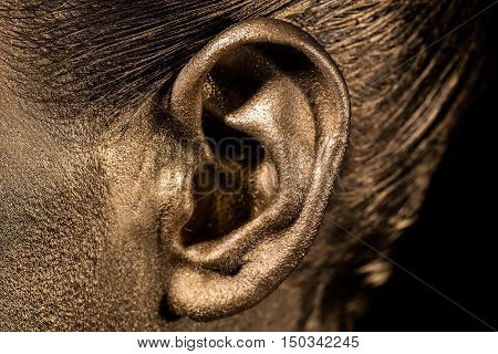 female golden or gold ear on face as makeup or body art painted metallized color closeup