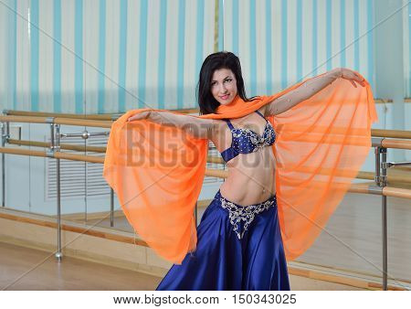 Beautifull caucasian woman in costume for belly-dance is dancing indoors at dance class.