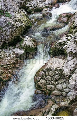Mountain stream detail cold freshwater running over rocks and stones