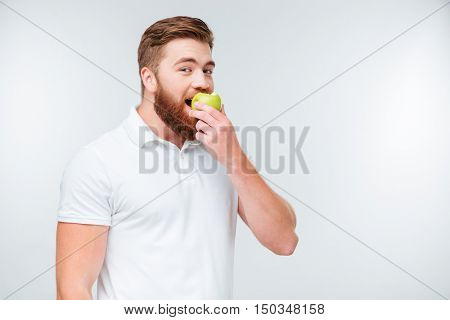 Cheerful young man is eating apple isolated over white background