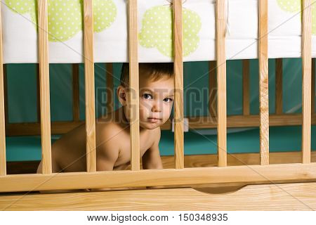 Naked little blonde boy with blue eyes hid behind a wooden lattice cot in children's room
