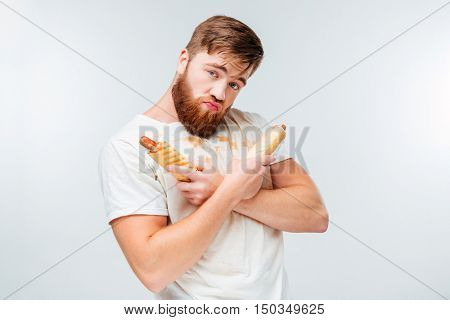 Young bearded man in filthy shirt holding two hotdogs isolated on white background