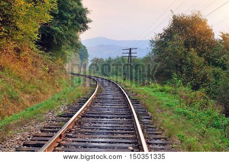 Railway track in a beautiful autumn forest fog. dampness bright warm autumn colors