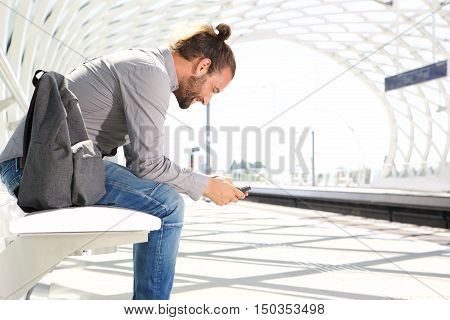 Traveling Man Waiting With Cell Phone At Train Platform