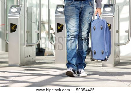 Low angle portrait of legs walking through ticket turnstile with luggage poster