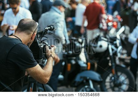 Back view of unrecognizable newstaper making video report about moto exhibition
