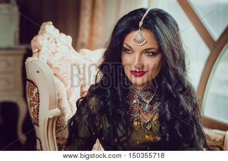portrait of a beautiful woman in Indian traditional Chinese dress, with her hands painted with henna mehendi