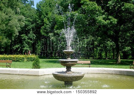 The photo shows a park fountain gushing. In the background you can see a park bench and tree covered with green leafs.