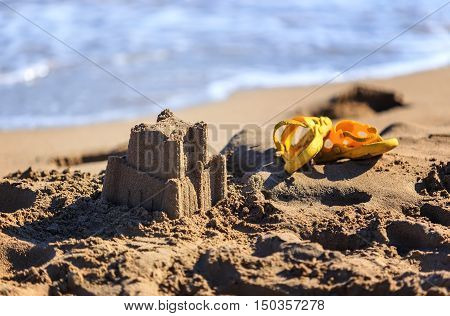 sand castle and children's flip-flops for the beach
