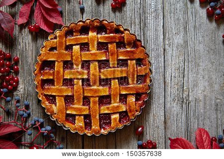 Homemade traditional sweet autumn raspberry tart pie with cream and mint on vintage wooden table background. Rustic style and natural light.