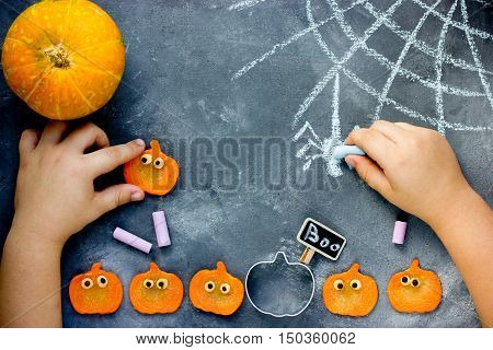 Preparing for Halloween - child draw with chalk cobweb and spider crafts process with kids top view