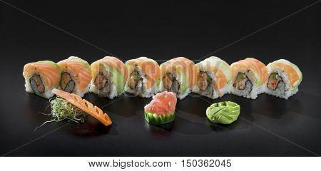 Japanese Sushi rolls. Uramaki maki sushi with salmon fresh seaweed salad and wasabi