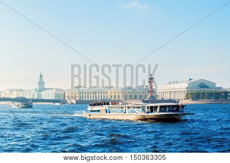 ST PETERSBURG RUSSIA-OCTOBER 3 2016. St Petersburg panorama - Neva river and St Petersburg landmarks of University embankment and Vasilievsky island with touristic sailboat in St Petersburg Russia