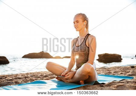Beautiful young woman with eyes closed listening music on beach