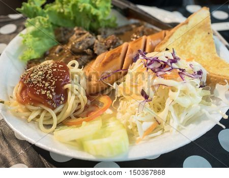 Grilled pork steak with sausage in plate.