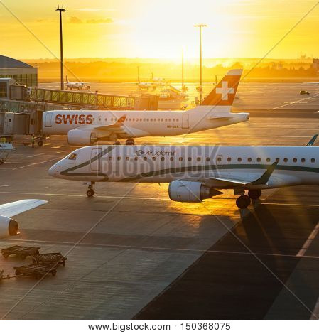 PRAGUE - August 13, 2016: Commercial airplanes at Vaclav Havel Airport Prague on August 13, 2016, boarding passengers in beautiful sunset